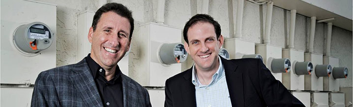 Isaias Sudit (left), CEO of GridGlo, and CFO Richard Viens, stand outside a row of smart meters, in Boca Raton, Florida.