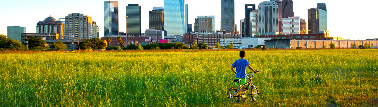 Child holding bike looking at Houston, Texas skyline.