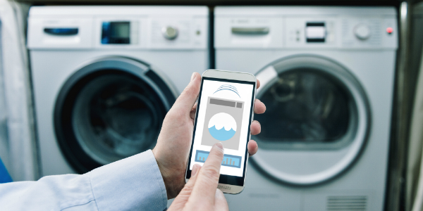 man operating smart washer and dryer with smartphone