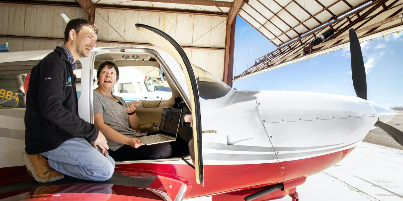 Scientists David Lyon and Mackenzie Smith talking in a small plane in hangar